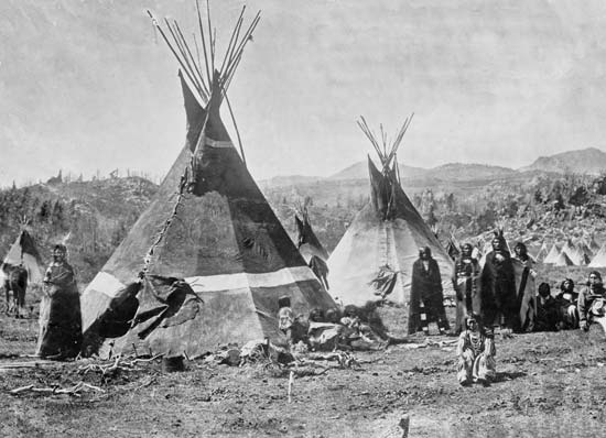 A group of Shoshone stand by their tepees in a photo taken in the early 1900s.