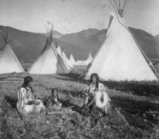 A photograph shows a group of Flathead Indians seated in front of tepees on their reservation in Montana in about 1908.
