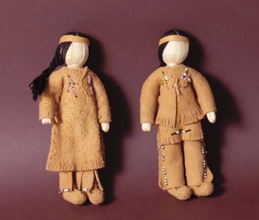 Two dolls show the styles of clothing once worn by the Apache people.