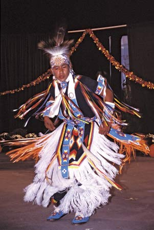 A Cherokee boy performs a dance in festive clothing.