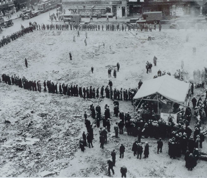 Unemployed workers wait in a long line at a soup kitchen in New York City during the Great Depression.