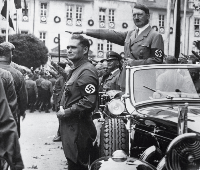 Deputy party leader Rudolph Hess stands in the foreground as Adolf Hitler gives the Nazi salute from a car at a parade in Weimar in 1936.