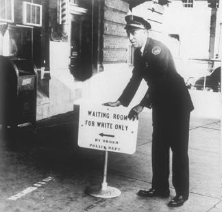 A police officer places a segregation sign in front of a railroad station on January 9, 1956, in Jackson, Mississippi.