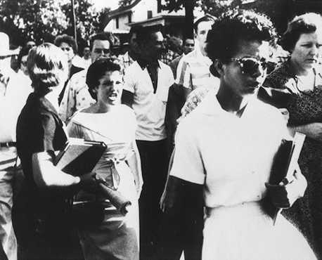 Elizabeth Echford walks to Little Rock High School with a crowd behin her in September 1957, shortly after the Supreme Court ruled in favor of desegregation. AP/Wide World Photos. Reproduced by permission.