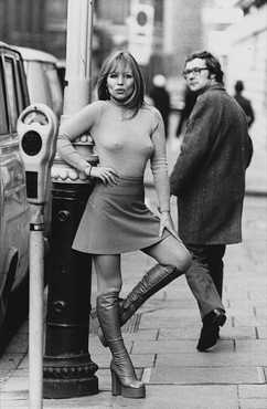 Model Susan Shaw turns heads of onlookers while wearing this ensemble of a miniskirt, ribbed polo-neck sweater, and platform-heeled boots in 1975.  Hulton-Deutsch Collection/Corbis-Bettmann.