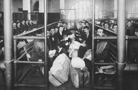 Early twentieth century immigrants to the United States sit with their luggage, waiting to be processed, on Ellis Island, New York. THE LIBRARY OF CONGRESS.