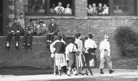 White students look on as African American students are escorted into Little Rocks Central High School by federal troops.  BETTMANNCORBIS. REPRODUCED BY PERMISSION.