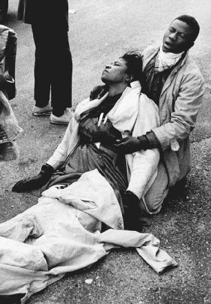 A young man is shown holding an unconscious woman after police broke up a peaceful march for voting rights that began in Selma, Alabama, in March 1965. Police used clubs, whips, and tear gas to stop the marchers. The police actions, as photogra