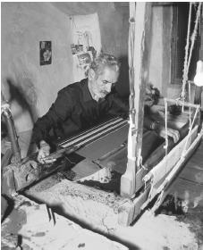 A carpet maker works on a loom at his shop in Nain.