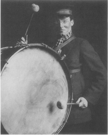 A Salvation Army volunteer bangs a drum in a production of Major Barbara