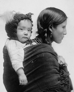 A 1901 photograph of a Native American mother from the Plains region carrying her baby on her back.