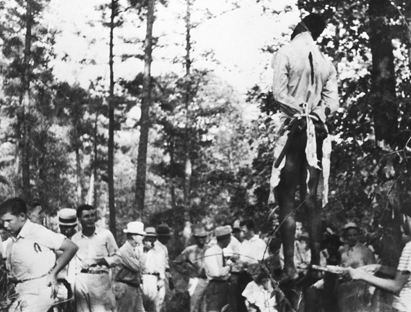 Lynching. A mob surrounds the body of a lynched black man