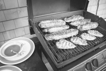 A backyard barbecue grill with pork meat on the slats and a bowl of homemade sauce on the side.