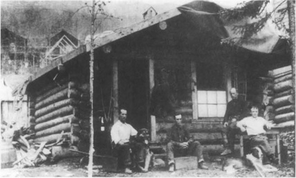 Marshall and Louis Bond with their dog, Jack, the inspiration for Buck in Jack Londons The Call of the Wild, sitting in front of a log cabin in the Yukon.