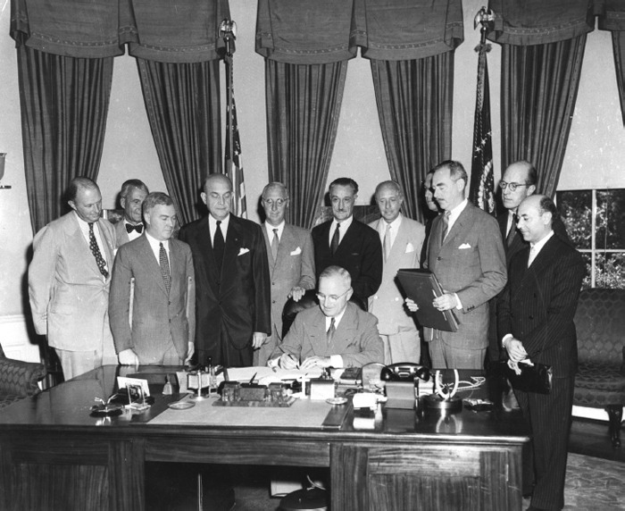 President Harry S. Truman signs the North Atlantic Treaty which marked the beginning of the North Atlantic Treaty Organization (NATO), behind him are (from left) Sir Derrick Hoyes Miller