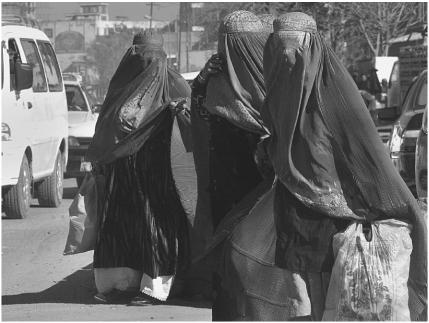 Burqa-clad Afghan women wait for a bus in Kabul, Afghanistan.