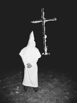 Members of the KKK dressed in white robes for secrecy and to create fear. A burning cross was it symbol of terror.