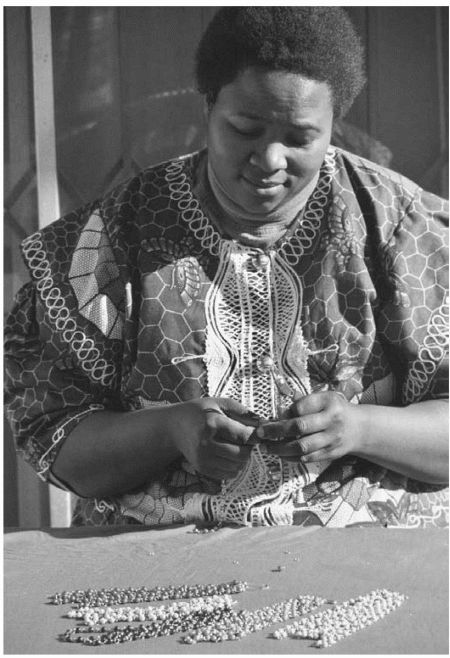 A Xhosa-speaking worker creates a necklace from beads at Umtha Beads, a craft business run by David and Cheryl Milligan. The couple started the business after David was laid off work as companies restructured in the new South Africa.