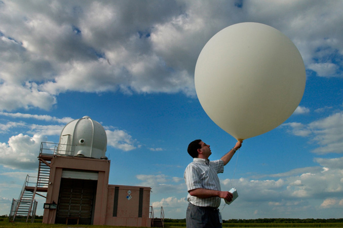 A meteorologist gets ready to launch a weather balloon.