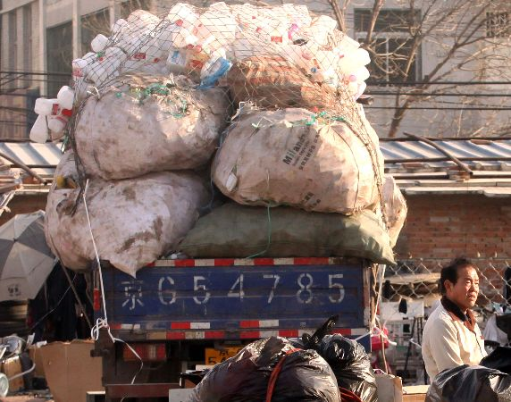 A Chinese man stands near his daily grab of recyclable trash at a garbage depot in Beijing February 14, 2011. Due to China's unprecedented rate of urbanization it now faces a daunting problem of urban waste.