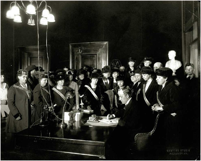 Suffragists look on as Kentucky governor Edwin P. Morrow signs the ratification billfor the Nineteenth Amendment to the Constitution, January 6, 1920.