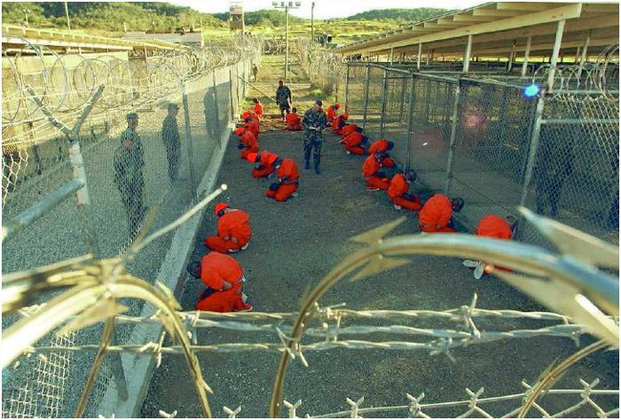 US military police guard suspected Taliban and al-Qaeda detainees at Camp X-Ray at Guantanamo Bay Naval Base, Guantanamo Bay, Cuba, January 11, 2002.
