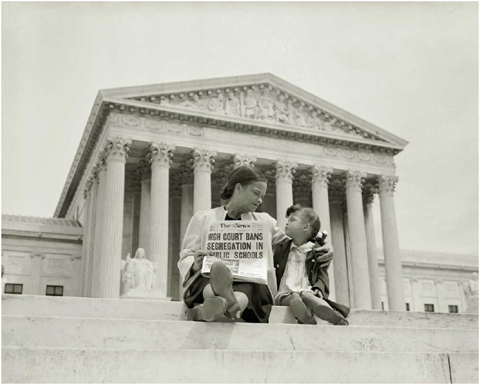 Holding a newspaper announcing the decision inBrown v. Board of Education, banning segregation in public schools, a mother sits with her daughter on the steps of the US Supreme Court, 1954.
