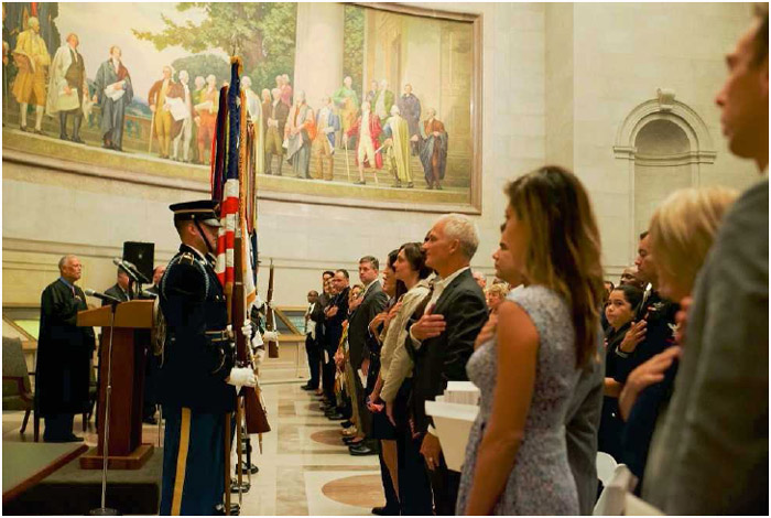 New citizens of the United States pledge allegiance to the flag at a naturalization ceremony held at the National Archives, September 17, 2014.