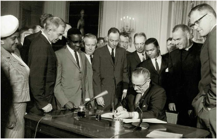 President Lyndon B. Johnson signs the Civil RightsAct into law at the White House, July 2, 1964.
