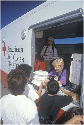 A Red Cross volunteer distributes meals from a disaster relief services van, ca. 1994.