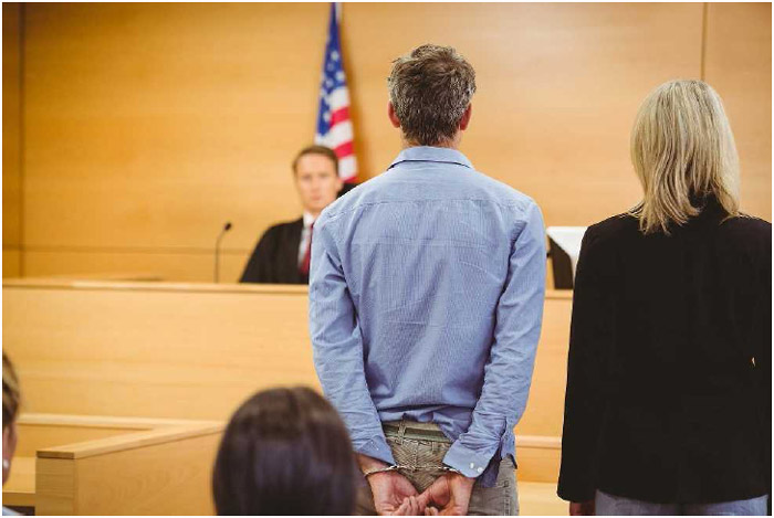 A defendant in a criminal case appears with his lawyer before a judge.