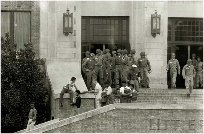 In the aftermath of the Supreme Court's school desegregation ruling, federalized Arkansas National Guard troops, on orders of President Dwight Eisenhower, protect African American students as they leave Little Rock's Central High School at the end of the school day, October 3, 1957.