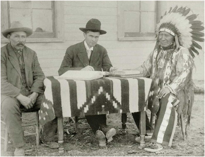 Chief American Horse, an Oglala Lakota Sioux, completes the paperwork to become an American citizen with a US surveyor and an interpreter, ca. 1907.
