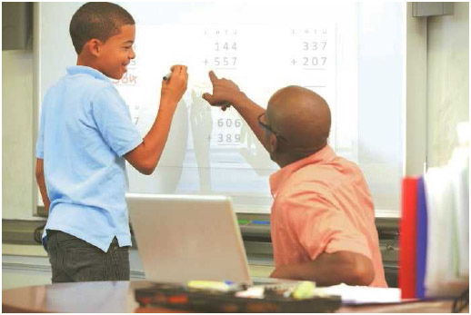 A student with attention deficit hyperactivity disorder receives one-on-one instruction with his teacher. The method of teaching students according to their own special way of learning is effective in managing ADHD.
