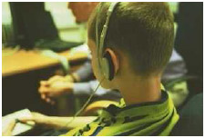 Boy taking part in an autism test that is analyzing his response to various facial expressions on a computer-generated face. People suffering from autism often have difficulty in judging the emotions reflected in different facial expressions.