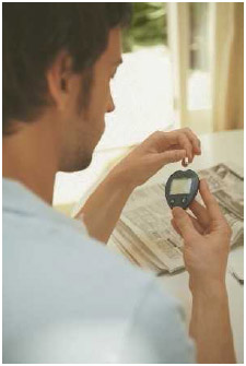 """Young man using a blood glucose meter at home. To measure sugar level, you prick your finger with a lancet to get a drop of blood. Then place the blood on a disposable """"test strip"""" that is inserted in the meter."""