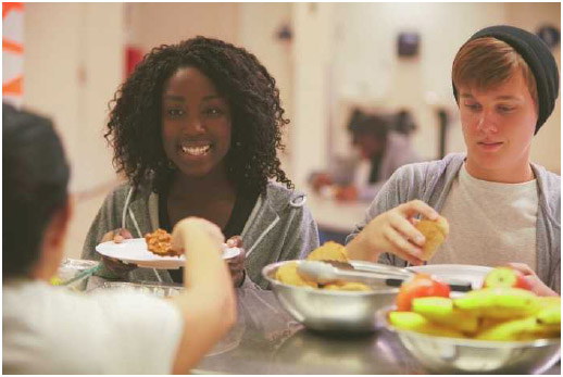Teens being served a meal at a homeless shelter.