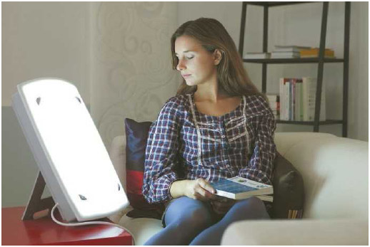 A patient uses light therapy to treat seasonal affective disorder (SAD).