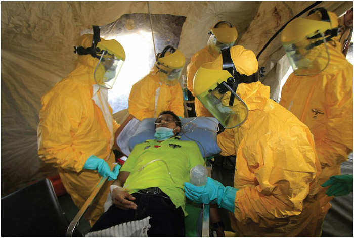 Indonesian health officials conduct simulation exercises for Ebola preparedness involving mock plane passengers during the Ministry of Health's 50th anniversary celebrations near the National Monument, Jakarta, Indonesia, on November 12, 2014. The World Health Organization on October 13, 2014, urged East Asian and Pacific countries to strengthen defenses against the Ebola outbreak. The region of 1.8 billion has been a hot spot for many emerging diseases, including severe acute respiratory syndrome (SARS) and avian influenza.
