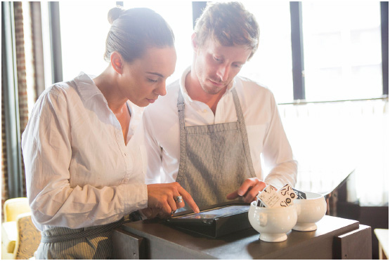 Two restaurant workers input customer orders using a tablet. Technological developments, such as the introduction of touchscreen tablets at the turn of the 21st century, are one component of the STEEPLE (social, technological, economic,