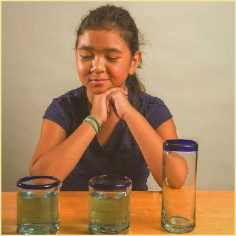 A child looks at identical glasses filled with the same amount of liquid to demonstrate Piaget's Liquid Conservation experiment