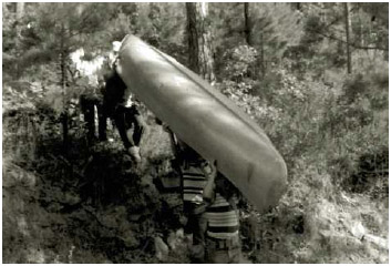 A group of boys work together to carry a canoe.