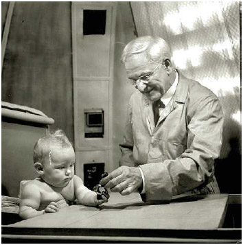 Dr. Arnold Gessell studying behavior of six months old baby by handing her a bell to see how well she uses her hands.