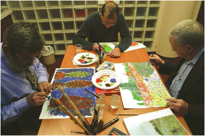 Three men participate in an art therapy session at a center for patients with Alzheimer's disease.