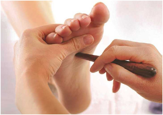 A woman uses a massaging tool to stimulate acupressure points in a person's foot. Acupressure techniques are used to release muscle tension, increase blood flow, and enhance the body's energy.