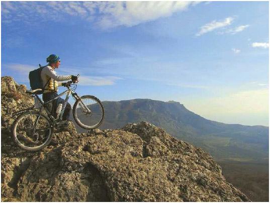 A bicyclist enjoys the view from a mountain top. Altitude training increases a person's red blood cell count as the body responds to receiving less oxygen when exercising.