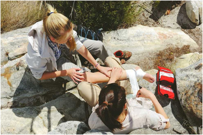 A woman uses medical gauze to wrap another woman's sprained ankle while on a hike. Most ankle sprains will heal on their own over time, but doctors recommend the R.I.C.E.