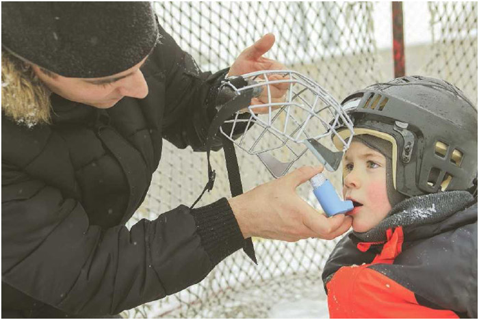 A man helps a young boy use his albuterol inhaler during a game of ice hockey.