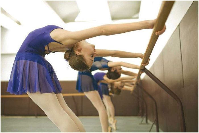 Several young ballerinas stretch using the ballet-barre. A standard feature of ballet and dance studios, the barre provides balance and stability to dancers during warmup exercises.
