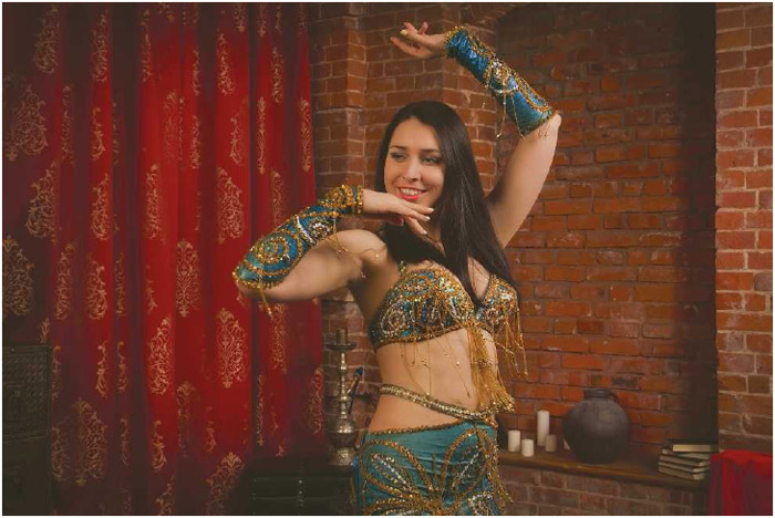 A woman bellydances in a traditional outfit. Bellydancing is a low-impact exercise, performed primarily by women, that can help with weight loss, muscle toning, posture, and relaxation.